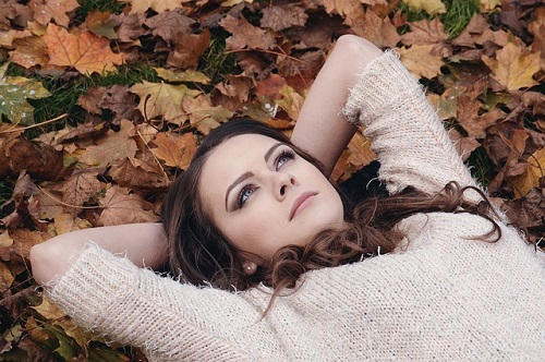 Woman lying on bed of leaves